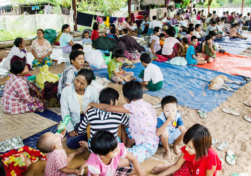 Families taking refuge at the Ka Lal Kone Village Monestary in Pwintbyu township wait for water levels to recede. (Aung Khant/The Myanmar Times)