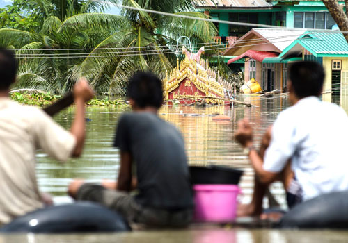 Local residents paddle around flooded Kalay in Sagaing Region on August 3. (Aung Myin Ye Zaw/The Myanmar Times)