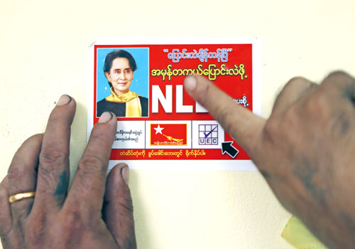NLD candidate Daw Khine Mar Htay places a campaign sticker with the image of Daw Aung San Suu Kyi in front of a house in Hlaing township yesterday. Photo: AFP