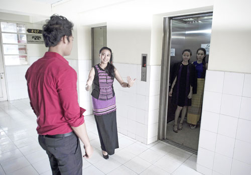 A student practices elevator manners next to Hla Nu Tun (right), teacher and founder of Style Plus H.