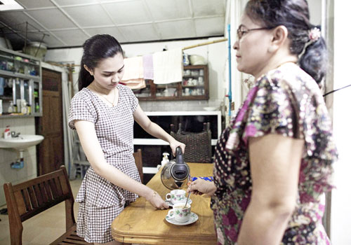 May Nandar Kyaw makes tea with her mother at their home.