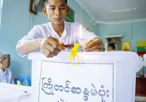 A polling station official seals a box used to accept advance votes at a polling station in Yangon on October 30. (Kaung Htet/The Myanmar Times)