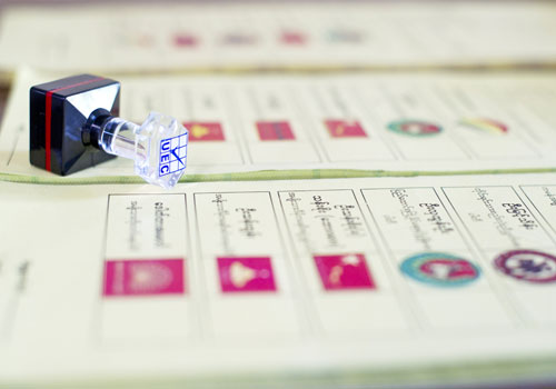 A Union Election Commission stamp sits on a ballot paper displaying the names of candidates at a polling station on the outskirts of Yangon on October 29. Photo: AFP