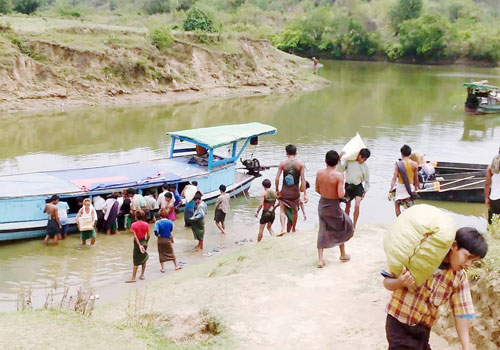 Aid supplies are unloaded from a boat in Sapa Seik village, Kyauktaw township, where more than 500 people displaced by fighting have taken refuge. Photo: Supplied