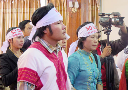 Activists wearing headbands calling for an end to dams on the Thanlwin River stand up during a public consultation for the 7000-megawatt Mong Ton Dam held in Taunggyi yesterday. (Lun Min Mang/The Myanmar Times)