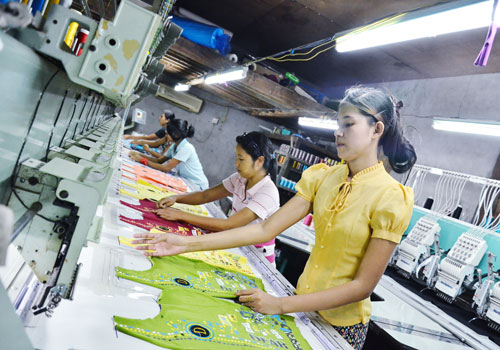 Workers attach beads to blouses at a garment factory on the outskirts of Yangon. (Aung Htay Hlaing/The Myanmar Times)