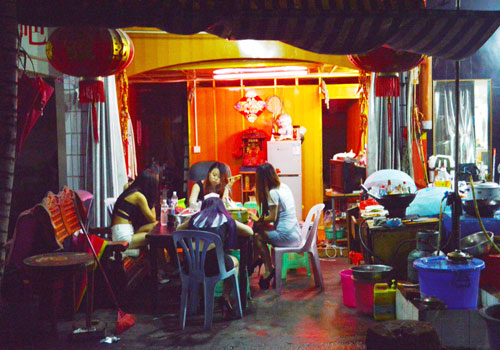 A group of sex workers sit in a shopfront brothel near Mong La's central market, waiting for customers.