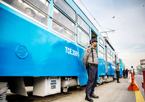 A police officer stands outside Yangon's new tram on Strand Road.(Aung Myin Ye Zaw / The Myanmar Times)
