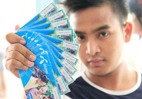A man holds a stack of Telenor mobile phone cards. Photo: Staff