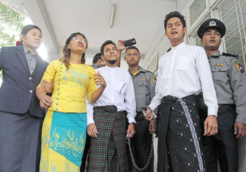 Ma Pwint Phyu Latt (second left), Ko Zaw Zaw Latt (third left) and Ko Zaw Win Bo (second right) stand outside a Mandalay court on February 26. Photo: Si Thu Lwin / The Myanmar Times