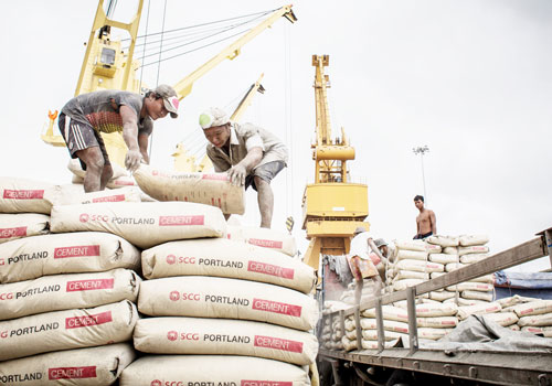 Workers load cement onto a truck at a port in Yangon. Photo: Zarni Phyo / The Myanmar Times