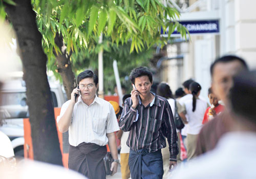 Two mobile phone users talk into handsets in Yangon. Photo: Staff