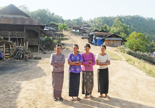 Women residents of Ngot Ngar village, Kutkai township, including Daw O Khe (left), stand in front of the homes they are defending. Photos: Fiona MacGregor / The Myanmar Times