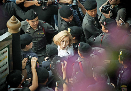 An activist is dragged away by police in Bangkok for defying a ban on public gatherings of five persons or more, and for protesting the recent arrest of several critics of the military regime, on April 27. Photo: AFP