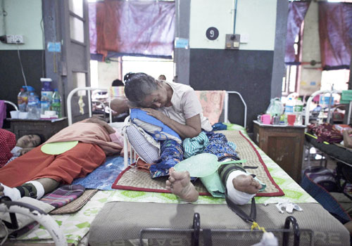A patient sleeps on her bed in a ward at Yangon General Hospital in Yangon. Photo: AFP