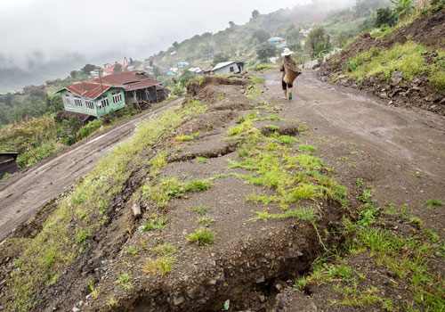 A resident walks by homes destroyed in a landslide in Hakha, Chin State. Photo: Aung Myin Ye Zaw / The Myanmar Times