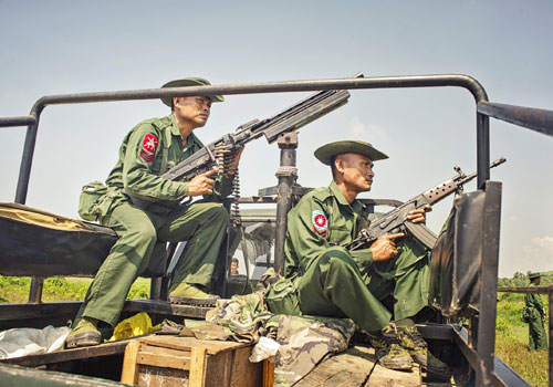 Tatmadaw soldiers take positions on a truck outside of Maungdaw town yesterday in Rakhine State. Photo: Kaung Htet / The Myanmar Times