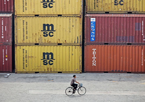 A man rides a bike past containers at Yangon port. The World Bank says improvements in port operations are needed to make doing business in Myanmar easier. Photo: Naing Lin Soe / The Myanmar Times