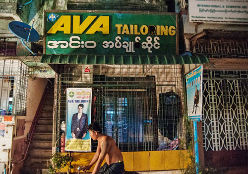 A trishaw drives past the Ava tailoring shop on 40th Street in Yangon's Kyauktada township on September 20. Photo: Aung Khant / The Myanmar Times