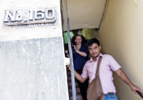 BBC reporters exit the stairwell at the address where a 47-year-old Briton was found dead on November 6. Photo: Zarni Phyo / The Myanmar Times