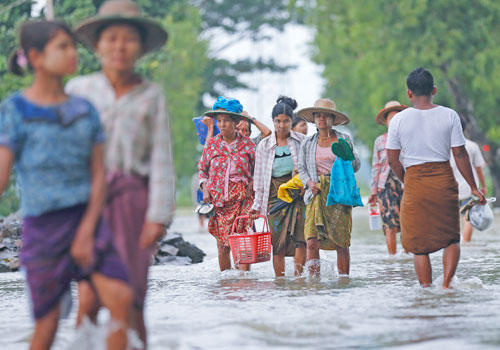 People walk through floodwater in Kyaunggon township of Ayeyarwady Region in August 2015. Photo: EPA
