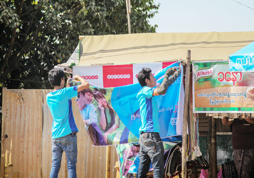 Men hang up a Telenor advert near an Ooredoo banner. Both firms are hoping to extend 4G services next year. Photo: Aung Myin Ye Zaw / The Myanmar Times
