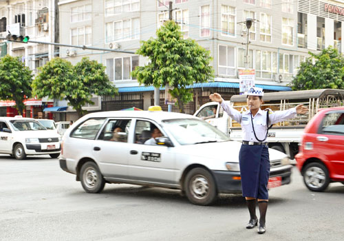 A police officer directs traffic at a busy intersectino in downtown Yangon. Photo: Aung Htay Hlaing / The Myanmar Times