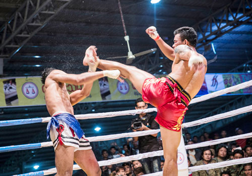 Myanmar's top flight lethwei fighter Too Too (right) delivers a high left kick to Thailand's Chanajon PK (left) in the January 6 New Year Challenge held in Mandalay's Diamond Plaza. Photos: Zarni Phyo / The Myanmar Times
