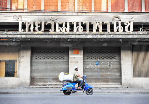 A scooter rider passes a derelict building of a bankrupt business in Bangkok. Many buildings remain derelict since the Asian financial crisis in 1997. Photo - Shutterstock