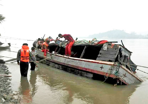 Personnel from the Fire Services Department and others help salvage the capsized boat. Yee Ywe Myint / The Myanmar Times
