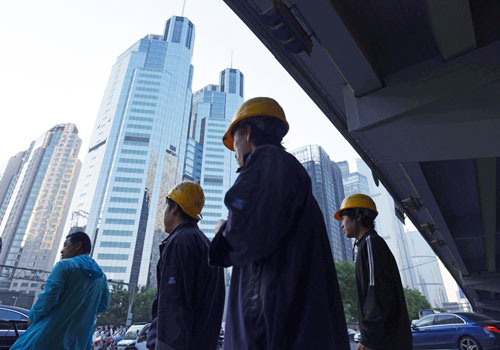 Construction workers wait to cross a road in the central business district of Beijing. Photo - AFP