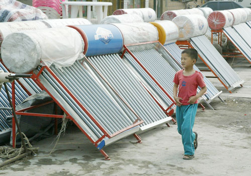A boy passes solar water heaters in Gaoliying village in the outskirts of Beijing. Photo - EPA