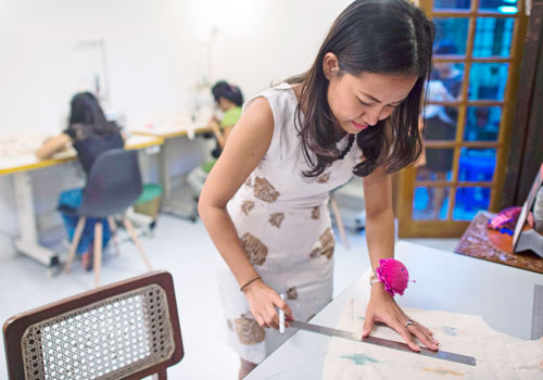 Pyone Thet Thet Kyaw (right), owner and designer of Virya Couture, working in her shop in Yangon. Photo - AFP