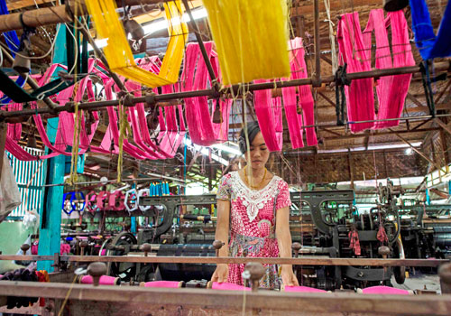 A woman worker weaving silk on a loom for traditional clothing in Mandalay. Photo - AFP