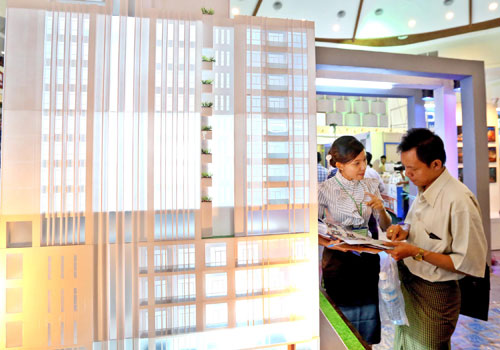 A buyer looks at a condominium model in Yangon. Similar units in Bangkok are expected to be well-received. Photo - EPA