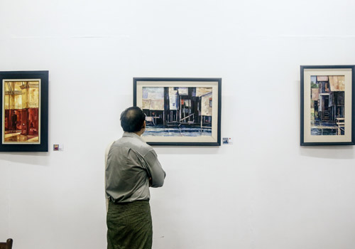 A viewer admiring some of the 40 paintings on show recently. Photos: Thiri Lu