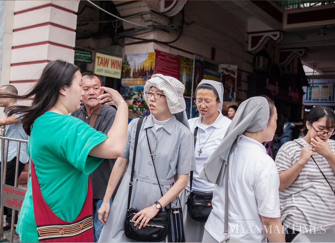 Tourists browse for merchandise at the Bogyoke Market in Yangon. Shin Moe Myint/The Myanmar Times