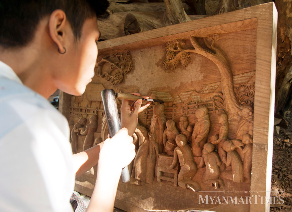 A wood sculptor works on a bas-relief for his sculpture.Photo: Shin Moe Myint