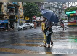A young couple shares an umbrella during a storm in Yangon. Photo: Theint Mon Soe/ The Myanmar Times