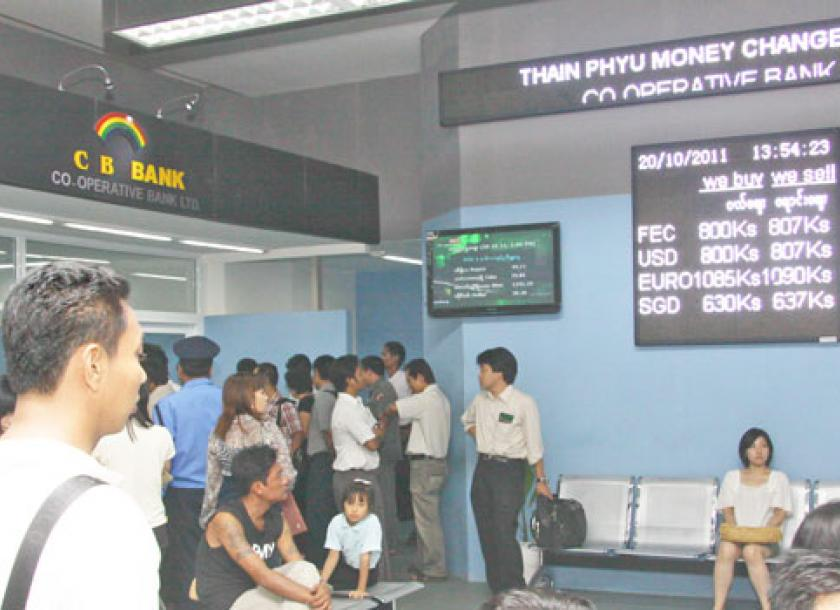 People Line Up To Change Money At A Foreign Exchange Counter On Thein Phyu Road In