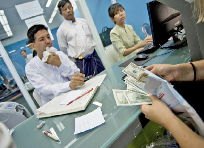 A Foreign Tourist Changes Money At An Official Exchange Counter On Thein Byu Road In