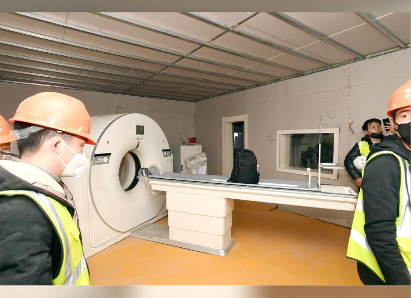 People walk near a CT scanner in a room at the Huoshenshan temporary field hospital in Wuhan in central China's Hubei Province, on Sunday. Photo - AP