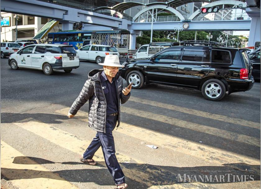 A man wears a jacket against the cold on Anawratha Road in Yangon. Photo: Myanmar Times
