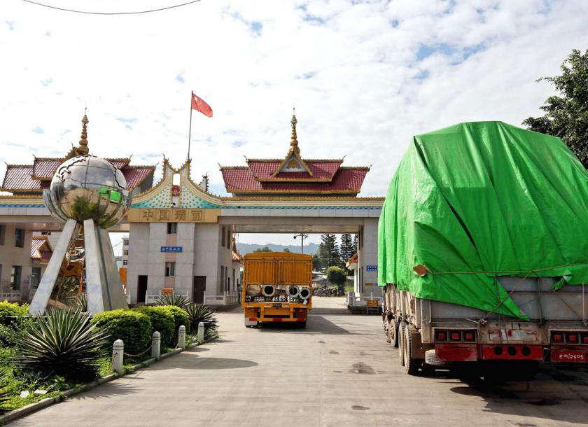 Loaded trucks with industrial goods wait to pass from China to Myanmar at the Kyegaung border gate, in Ruili, Yunnan province. Photo - EPA