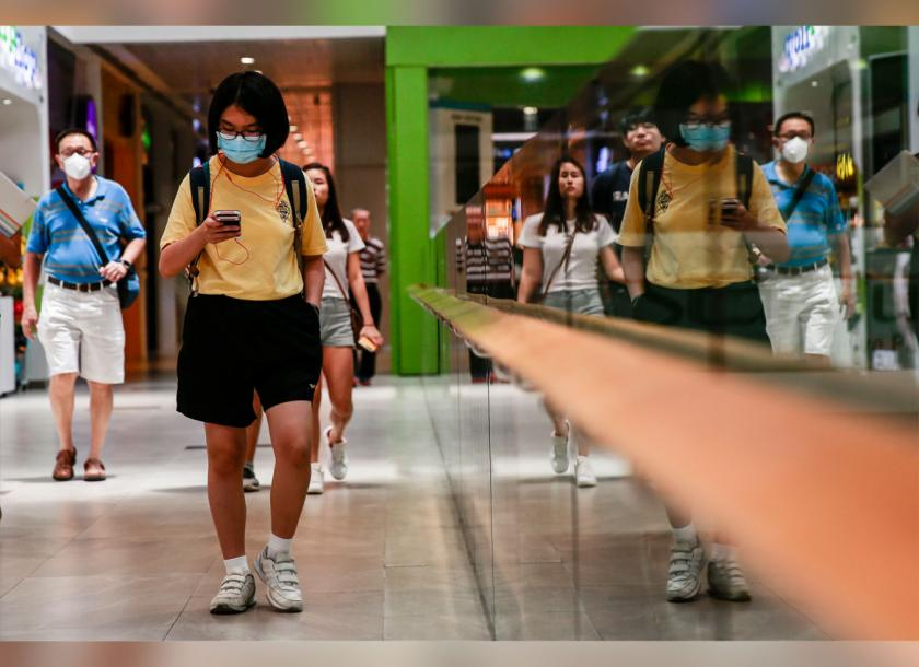 People wear masks while walking around a shopping mall in Singapore on Friday. Photo: EPA