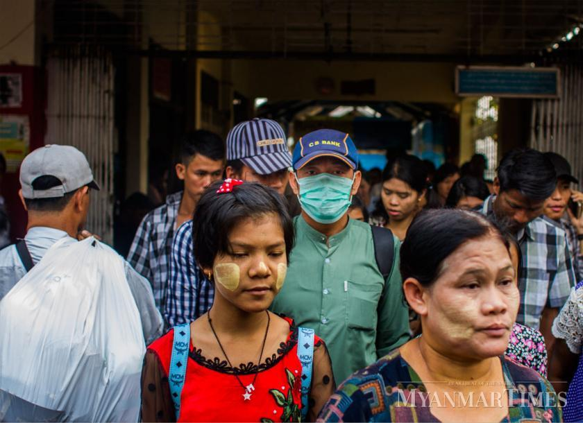 A man wears mask as he walks in a crowded jetty in downtown Yangon on Sunday. Photo: Mar Naw/The Myanmar Times