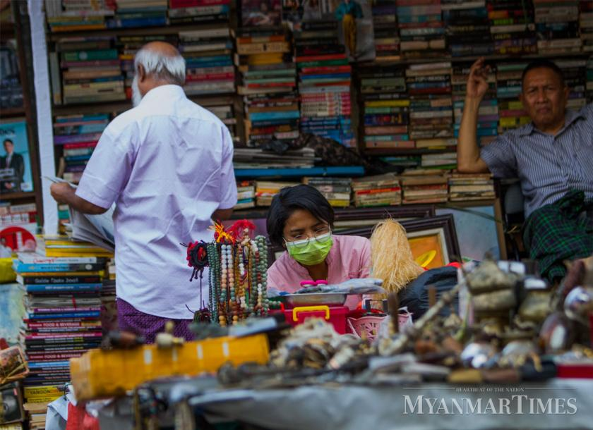 An accessory seller wearing mask wait for buying customers in Yangon's Bogyoke Market. Photo: Mar Naw/The Myanmar Times