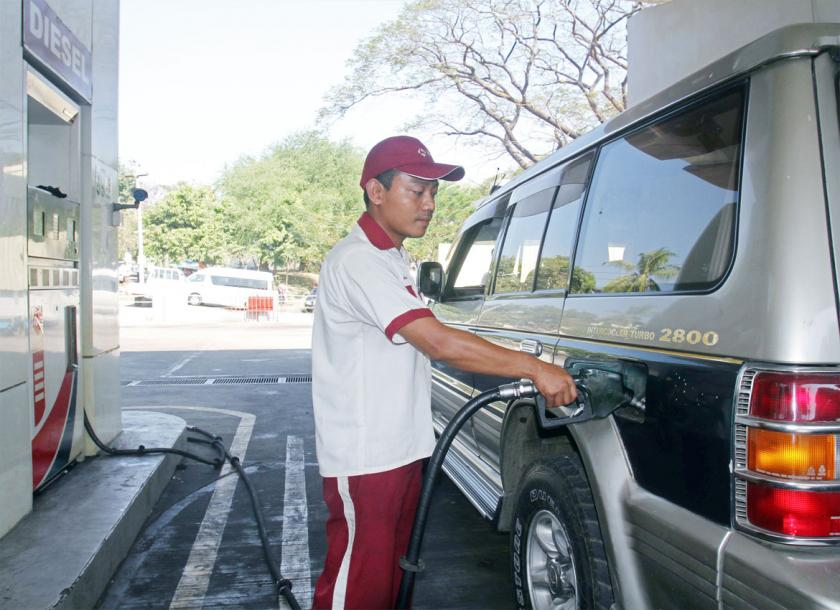 A file image of an attendant filling a vehicle at a petrol station in Yangon. Fuel prices have been dropping since the beginning of the year. Photo - EPA