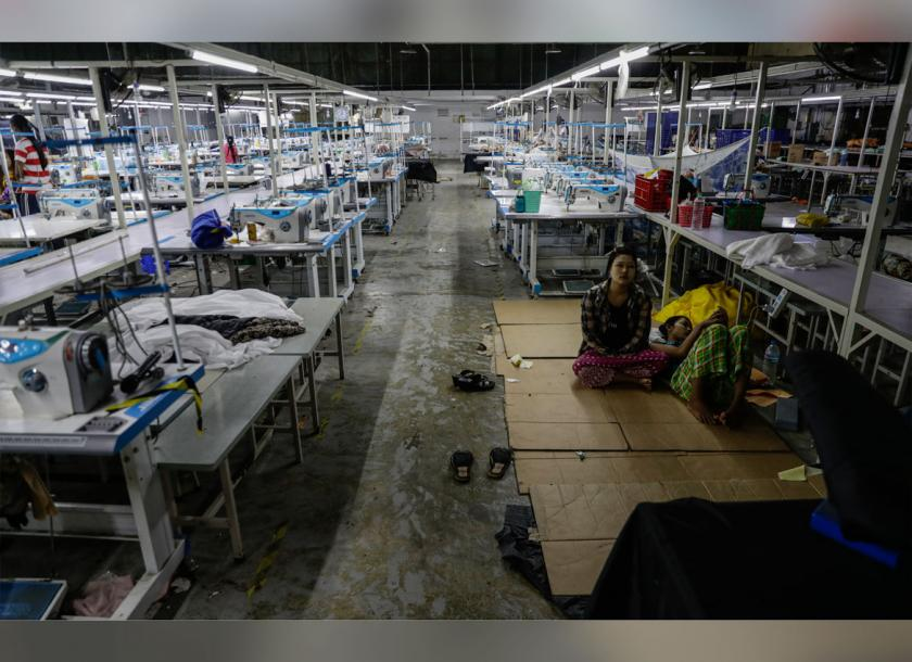 Workers near sewing machines in a closed garment factory near Yangon. The workers were seeking to claim their salaries and overtime pay on March 8. Photo: EPA