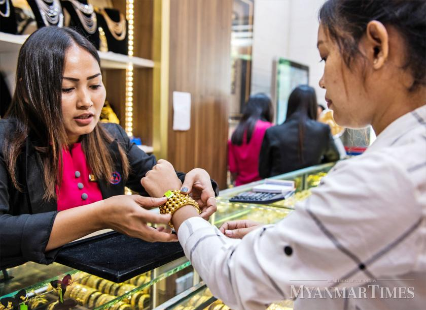 A Customer Inspects Gold Jewelry At Yangon Aung Htay Hlaing The